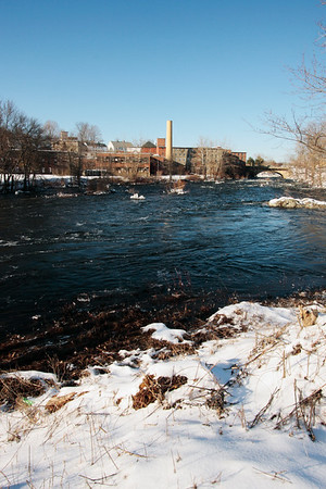A vertical stock photo of the old Mills in Putnam Connecticut,looking across the Quinebaug River on a sunny Winter day.