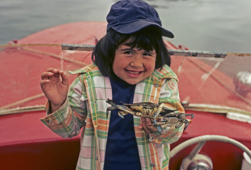 A horizontal stock photograph of A pretty little Filipino-american girl holding a live blue crab in her hand.