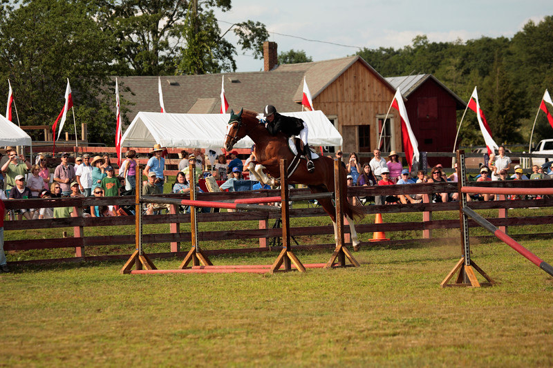 A horizontal stock Photograph of a woman starting to jump her horse over a double four foot jump.