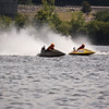 Two boats racing side by side. The high speed causes large plum of water behind them.