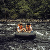 A horizontal stock photograph of two boys floating in a large tube down the Farmington River,Connecticut.