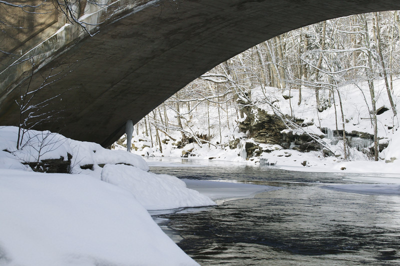 A horizontal stock photograph of the Natchaug River in winter with the view framed by the arching bridge over the river Located in Eastern Connecticut.