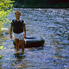 Young boy returning upriver from his tubing run