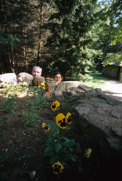 Older man and young boy heads peeking up behind a flower bed