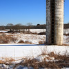 A Vertical Stock Photograph of an old grain silo setting in a snow covered field off Scenic route 169 Canterbury Connecticut.