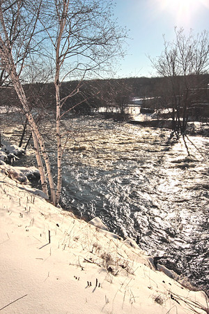 A vertical stock photo of the Quinebaug river in Putnam Connecticut. A contrasty winter day.