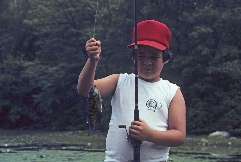 A horizontal stock photograph of a young boy holding his fish and his fishing rod.