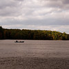 A vertical stock photograph of a man and a young boy fishing from a canoe on Mashapaug Lake Union Ct..