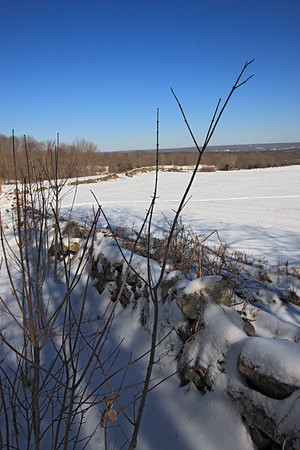 A Vertical Stock Photograph of fields and stone walls covered with snow off scenic Route 169 in Canterbury Connecticut.