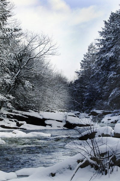A vertical stock photo of the Natchug River covered with snow and ice. Located in Eastern Connecticut.