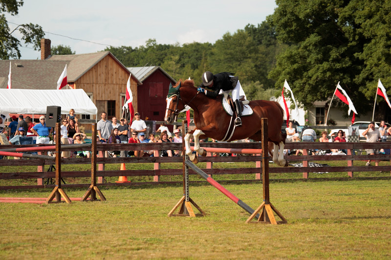 A horizontal Stock Photograph of a woman jumping her horse over a single four foot jump.
