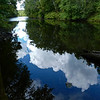 A horozontal stock photograph of the Quinebaug river in Eastern Ct. Reflections of puffy white clouds.