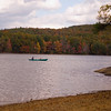 A vertical stock photograph of a man and young boy fishing from a canoe.A beautiful autumn afternoon in New England.. Mashapaug Lake Union Connecticut.