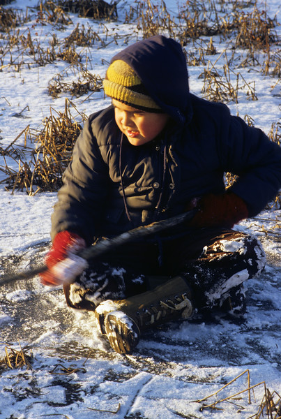 A vertical stock photograph of a young boy setting on the ice,playing a game with his stick on a sunny winter day.