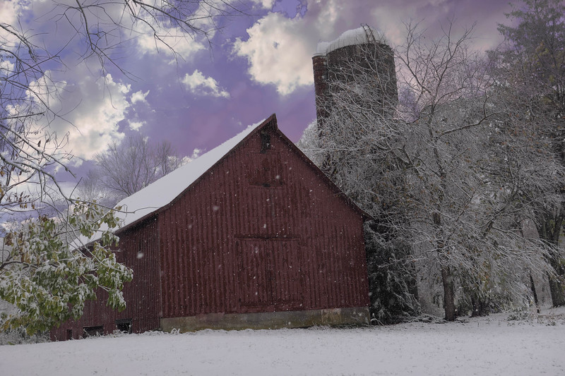 Red Barn and silo in         an Autumn snowfall.