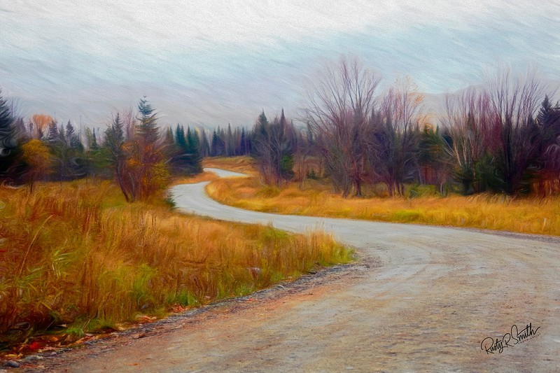 Winding dirt road through New Hampshire autumn landscape .