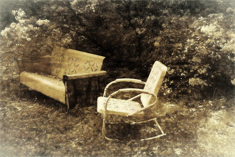 A vintage outdoor glider and chair.