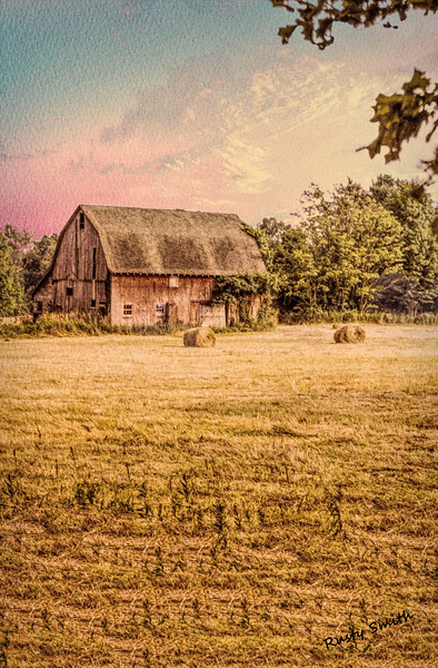 Old barn with round hay bales