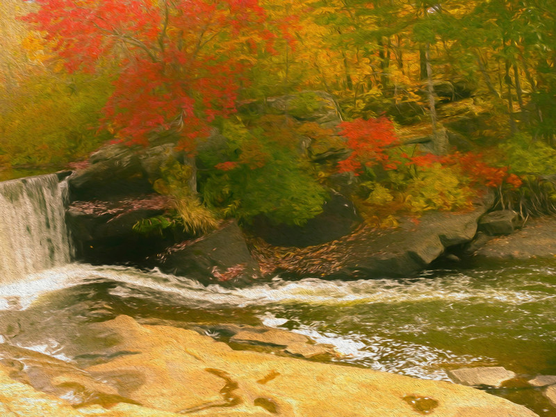 A small waterfall surrounded by bright fall color.
