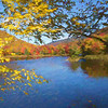 An Art photograph of a pond with bright fall colors on the shoreline.