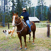 A woman sitting on a horse with St. Bernard dog looks on. Bear Creek  Guest Ranch Montana.