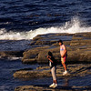 A preteen aged boy and girl playing in the surf of the rocky coast of Maine.