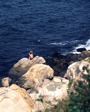 Young boy ocean fishing from the rocks