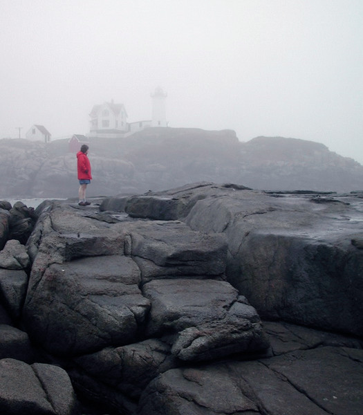 A vertical stock photo of Nubble Lighthouse in Southern Maine shrouded in fog  with woman wearing a red jacket in foreground. Showing strong rocky foreground.