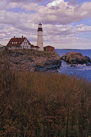A vertical stock photo of the Portland Head Lighthouse in Portland Maine. Grass and rocks in foreground.
