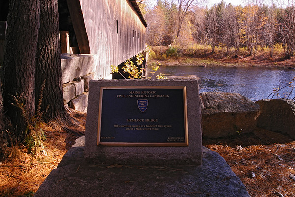 A horizontal stock photo of the stone signage in front of Hemlock Covered Bridge near Fryeburg Maine. Bridge spans the old course of the Saco River.