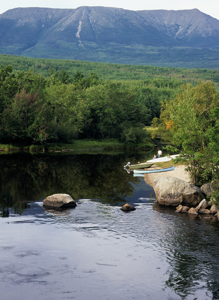 Looking across small pond with Mt. Katadin Maine in the background. A couple with boat and canoe in the foreground.