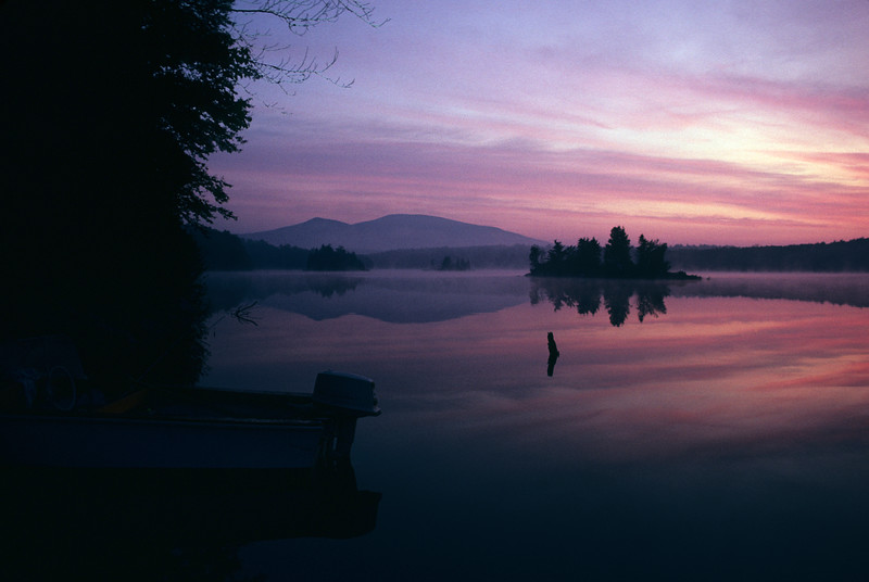 A horizontal art photograph of sunrise over Sebago Lake Maine.With power boat in foreground. Mountains in background.