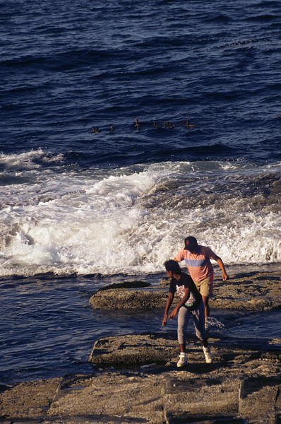 A preteen aged boy and girl running in the surf of the rocky coast of Maine.