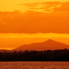 A horizontal stock photograph of a brilliant sunset over Brassua Lake in northern Maine.