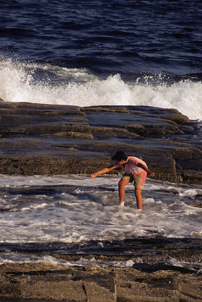 A preteen aged boy playing in the surf of the rocky coast of Maine.