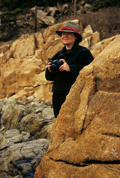 A smiling woman holding her camera while stand among large boulders.