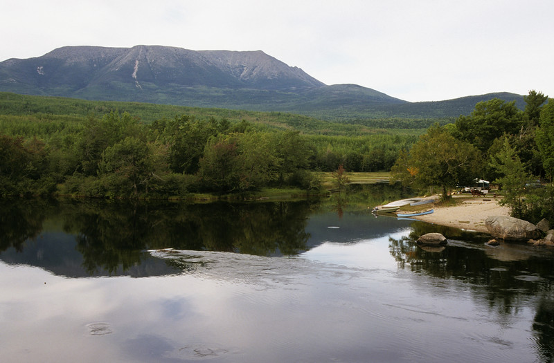 EDITORIAL USE ONLY A horizontal view looking across a small pond with Mt. Katadin Maine in the background,a campsite with boat and canoe in the foreground.