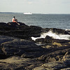 A preteen aged boy a ship pass by off the rocky coast of Maine.