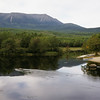 A wide view looking across a small pond with Mt. Katadin Maine in the background,a campsite with boat and canoe in the foreground.