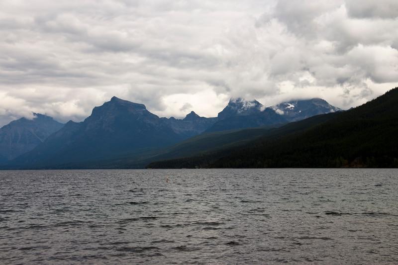 A horizontal stock photograph of mountains surrounding Lake McDonald. Low hanging clouds.  West Glacier Nat. Park.