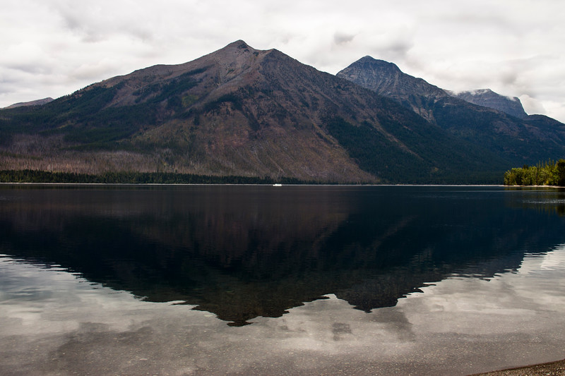 A horizontal stock photograph of mountains reflecting in Lake McDonald. A tour boat passing by in background.  West Glacier Nat. Park.