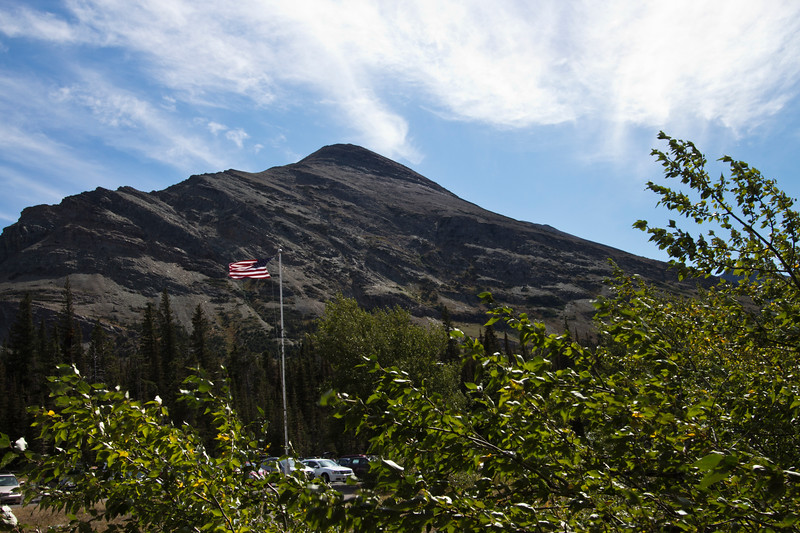 A horizontal stock photograph of  the mountains surrounding the Two Medicine area of Glacier National Park. Parking area of concession buildings with american flag in foreground.