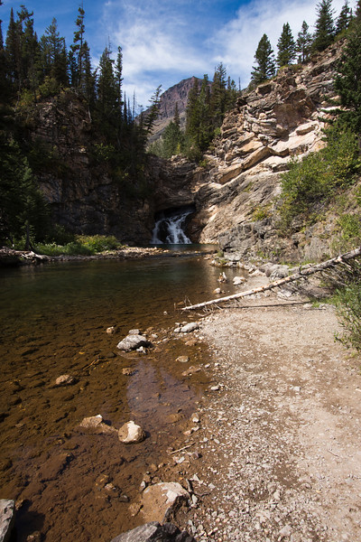 A vertical stock photograph of Running Eagle Falls in the two medicine area of Glacier Nat. Park Montana.