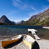 a horizontal stock photograph of Two Medicine Lake ,Glacier National Park, surrounded by mountains. canoes and tour boat in foreground.