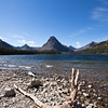a horizontal stock photograph of Two Medicine Lake ,Glacier National Park, surrounded by mountains. Driftwood in foreground.
