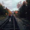 A vertical stock photograph of a man walking on railroad tracks enjoying the fall foliage.