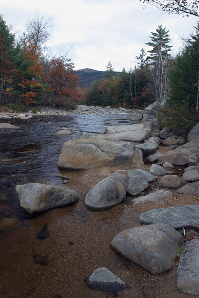 A vertical  stock photograph of the Swift river in White Mountains New Hampshire. Large rocks in the foreground.