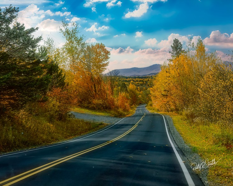 Route three in Northern New Hampshire winding through  fall foliage.