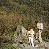 A vertical stock photograph of two young men standing on large rocks overlooking a valley in the white mountains New Hampshire