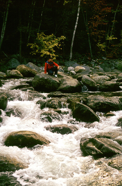 A Vertical Stock Photograph of a young Filipino American boy sitting on a large boulder in the middle of a rushing stream. White Mountains of New Hampshire